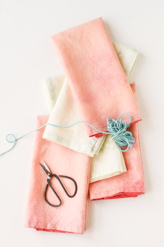 Pink and pastel napkins stacked up on a white table.