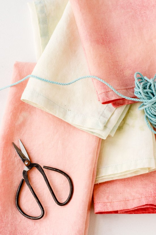 Stacked napkins in pastel colors with scissors and string.