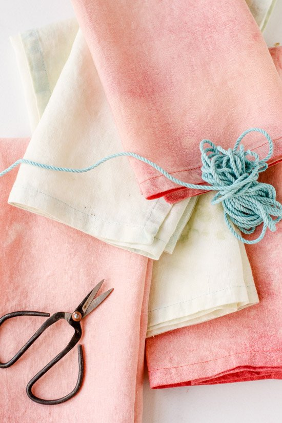 Pretty pink and pastel linens closeup, with scissors and thread.
