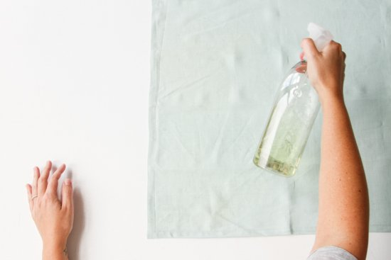 Spraying linen mint colored napkin with bleach for a lighter color textile.