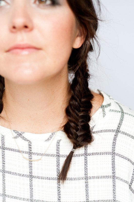 Closeup photo of fishtail braid pigtails on young woman with brunette hair.