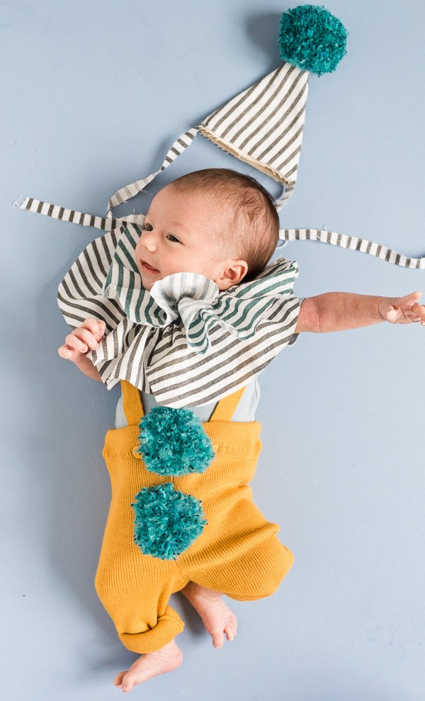 DIY Clown Costume for Baby. Complete with DIY pom poms, and a ruffly fabric collar and hat.