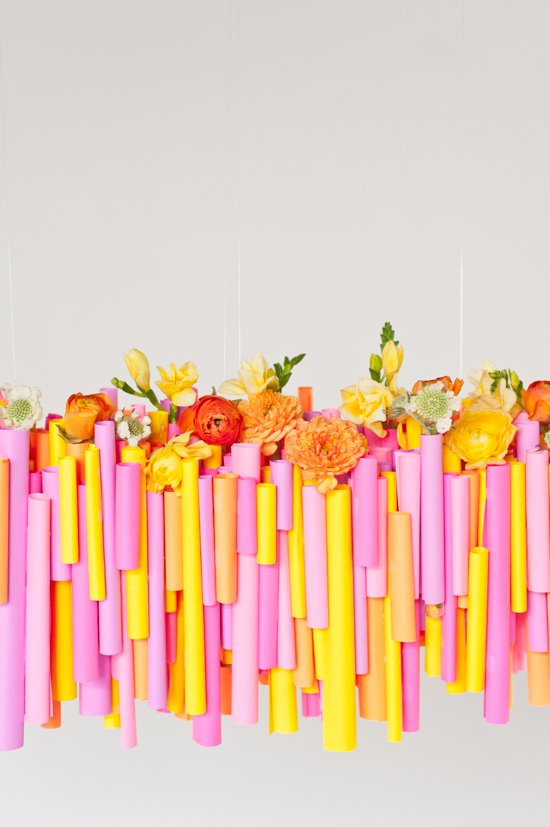Make this DIY hanging chandelier made of rolled up pieces of paper and wrapped test tubes for vases.