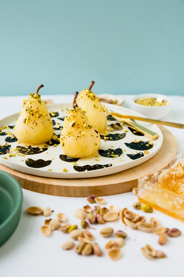 Recipe for boozy poached pears with drizzled honey and pistachios