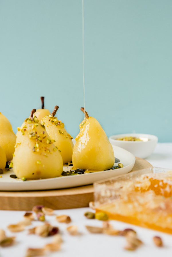 Boozy poached pears with drizzled honey and pistachios