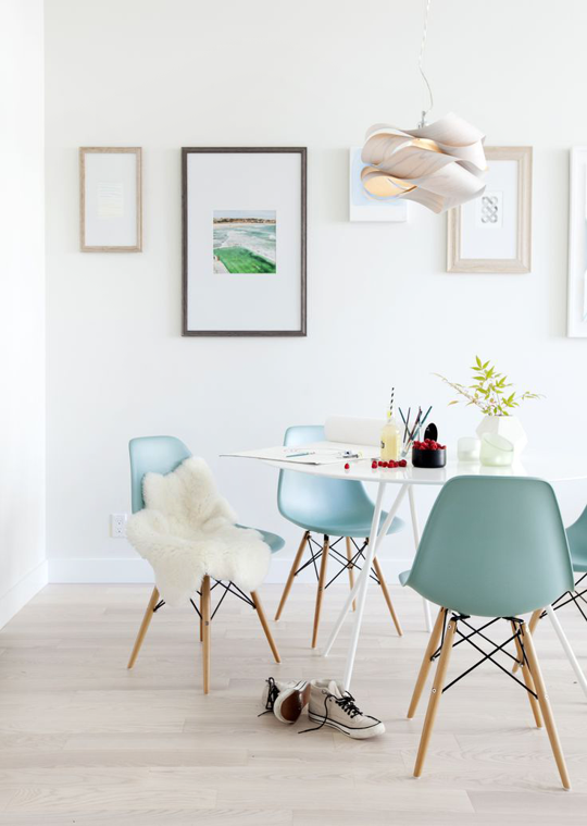 Light and bright dining space with blue Eames chairs and a simple white table.