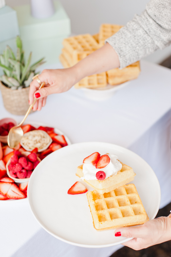 A waffle bar with fresh fruit and whipped cream for a DIY Mother's Day brunch