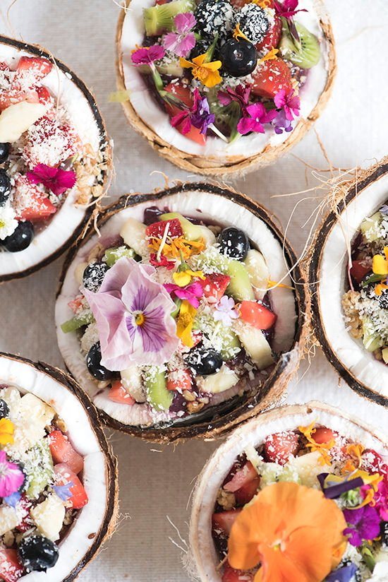 acai bowl in a coconut with edible flowers