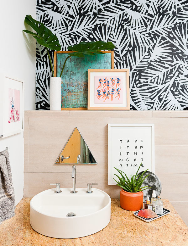 Guest bathroom makeover with cool artwork and wallpaper