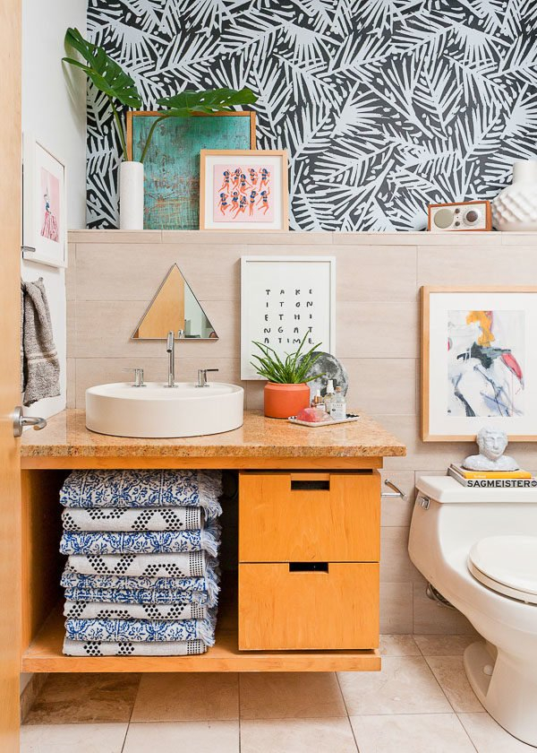 Cool guest bathroom makeover with quirky artwork and fun wallpaper