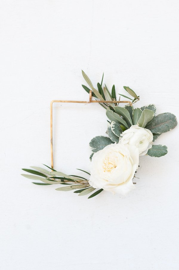 A white wreath with fresh garden roses, ranunculus, and olive branch greenery.