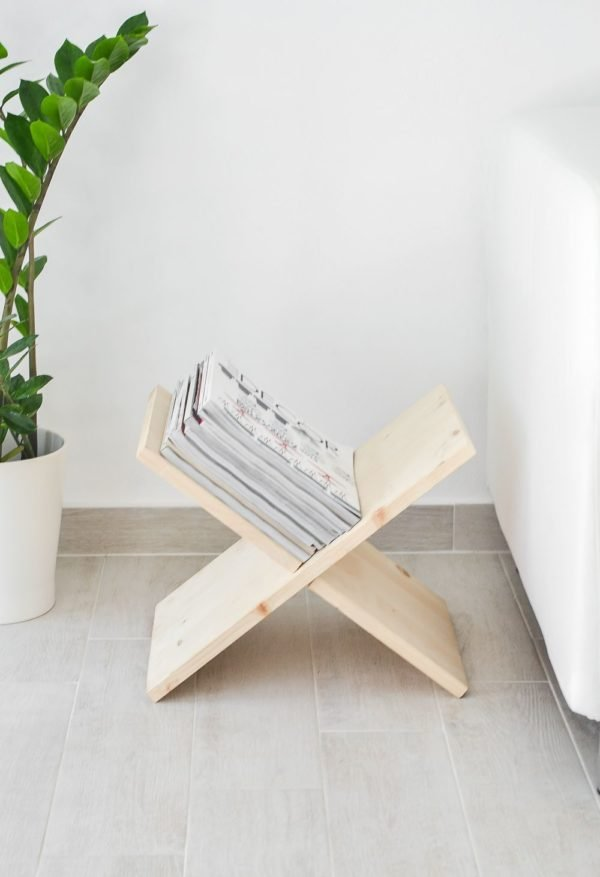 A wood magazine rack shaped like an X for storage, sits next to a couch.