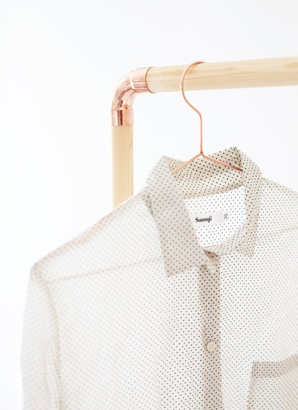 DIY clothing rack made of wood dowel rods and copper piping, with shirt hanging from it