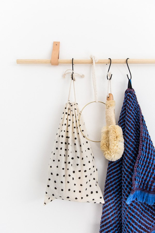 A wood and leather organizer in the bathroom, with a blue waffle towel hanging from an S hook.