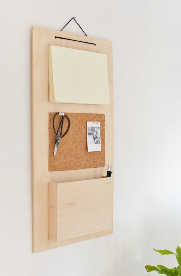 A hanging wall organizer made of wood and cork, with scissors hanging from it.