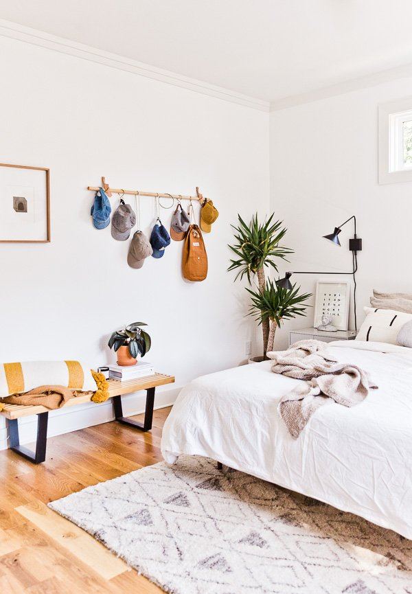Minimal, earthy bedroom with wood hanging storage for hats and bags.