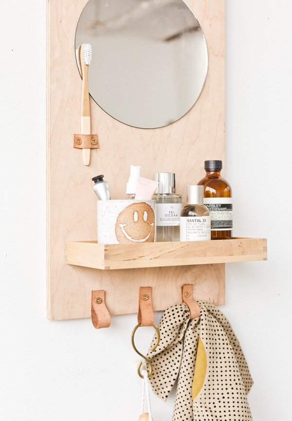 A wood wall organizer for the bathroom with round mirror and leather loops for towels