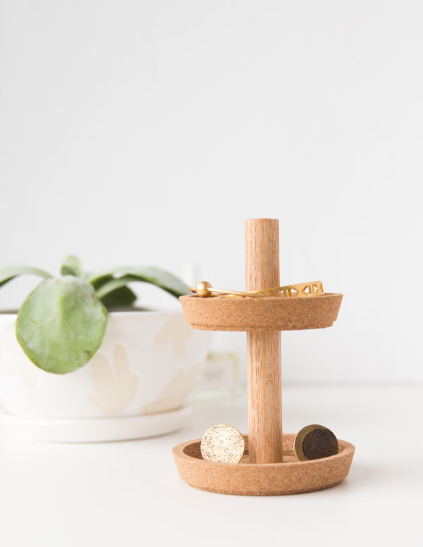 A small wood and cork jewelry holder sits on a plain white table.