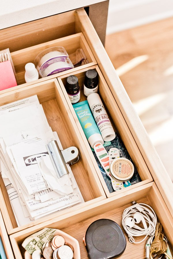 Organizing a junk drawer with drawer organizers to keep receipts and other items clutter-free