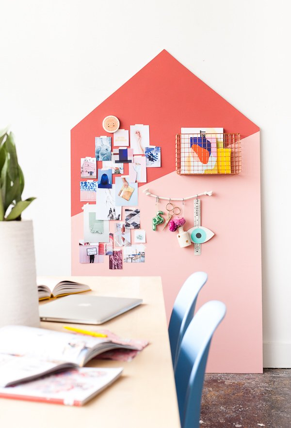A pink color blocked organizer leans against the wall in a large loft space.