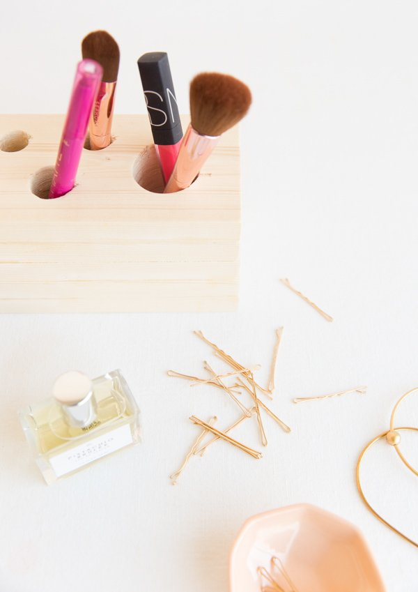 A wood makeup caddy with makeup brushes and lipgloss inside the top holes.