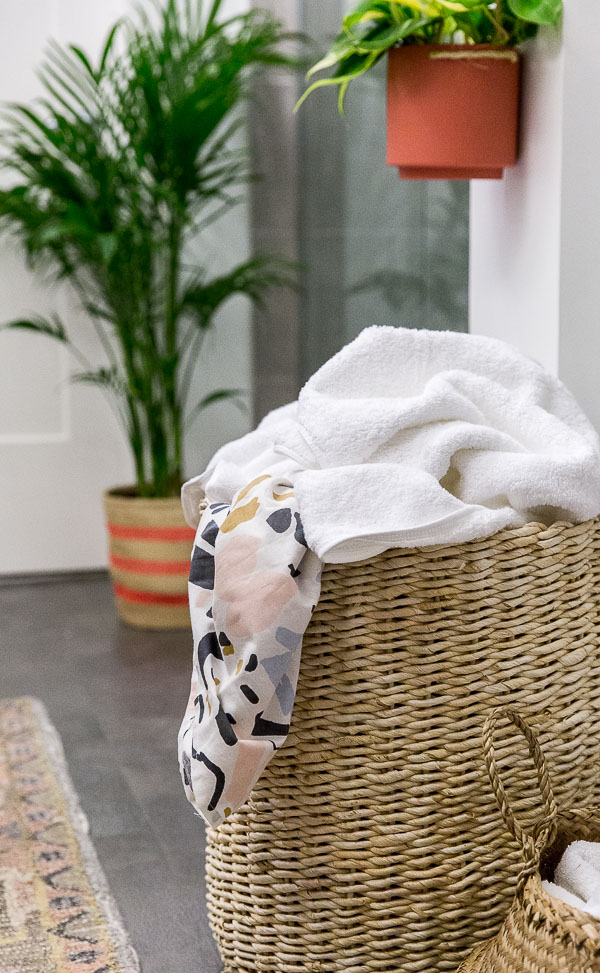 Use a large basket as a hamper in the bathroom for easy access to dirty clothes, etc. Click through for more tips and a before and after minimal modern bathroom makeover.