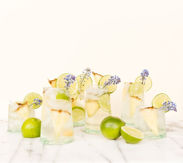 A tropical cocktail recipe for pineapple lime sangria spritzers, with edible flower garnish.
