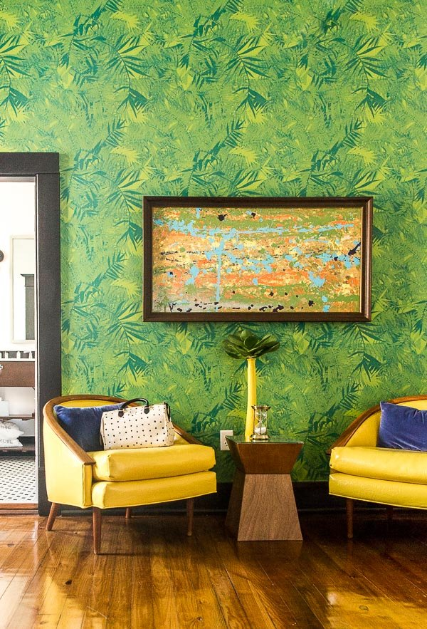 Tropical vibes with yellow chairs and palm frond wallpaper