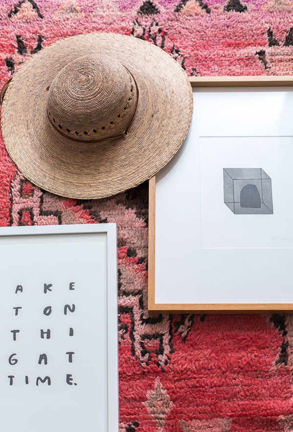 Minimal artwork and a colorful rug for an entryway