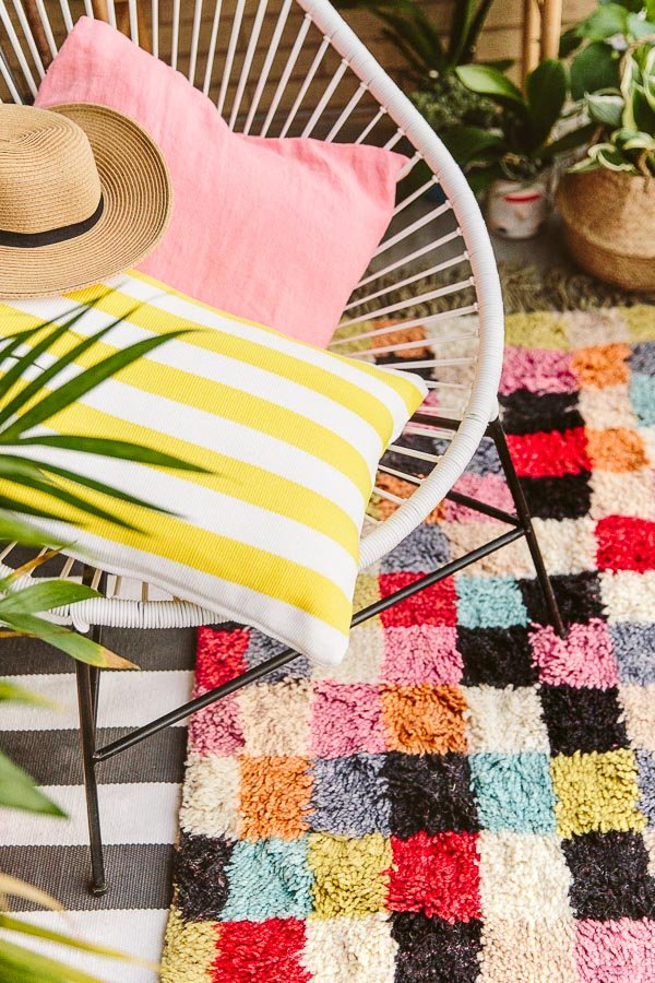 A small but colorful balcony makeover, with lots of plants and layered patterns.