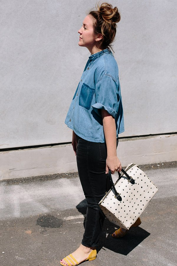 Cropped jean shirt, black jeans, and a big bag.