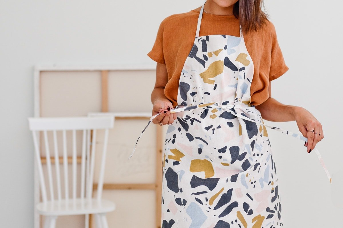 How to make a DIY apron. Terrazzo print apron being tied.