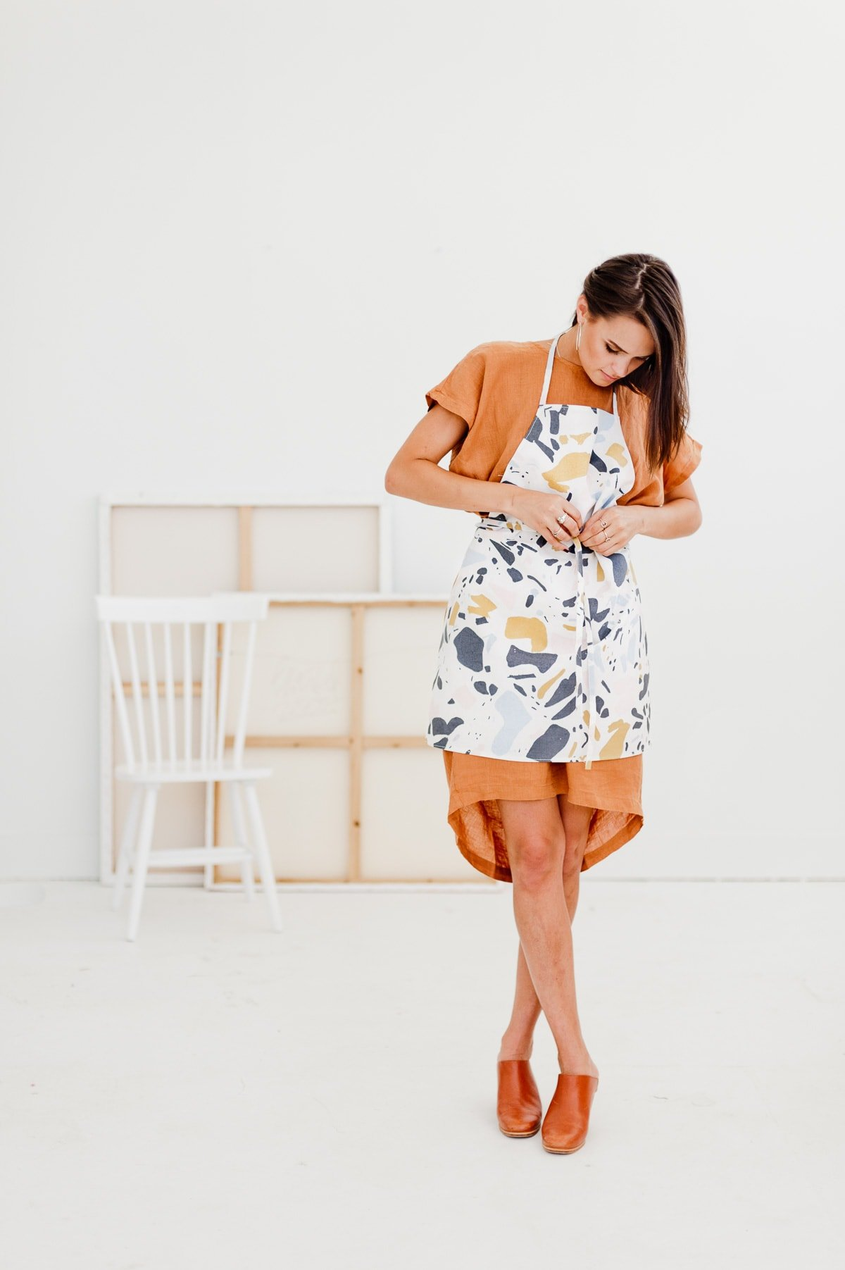 Woman tying terrazzo print apron in all white artist loft.