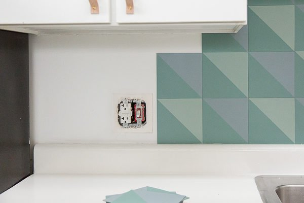 Install the DIY budget backsplash, using the painted pattern tiles you made.