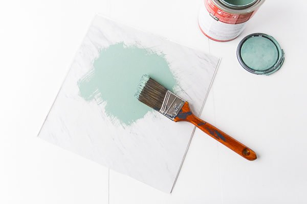First, paint the vinyl tile a solid color with (matte finish) house paint.