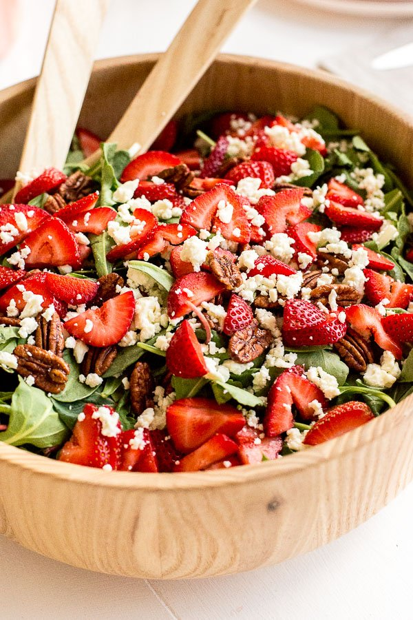Closeup of a summertime salad recipe made with strawberries and pecans.