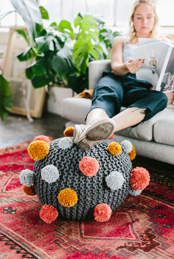 How to make a pom pom DIY ottoman with just a few supplies. #pompom #ottoman #falldecor