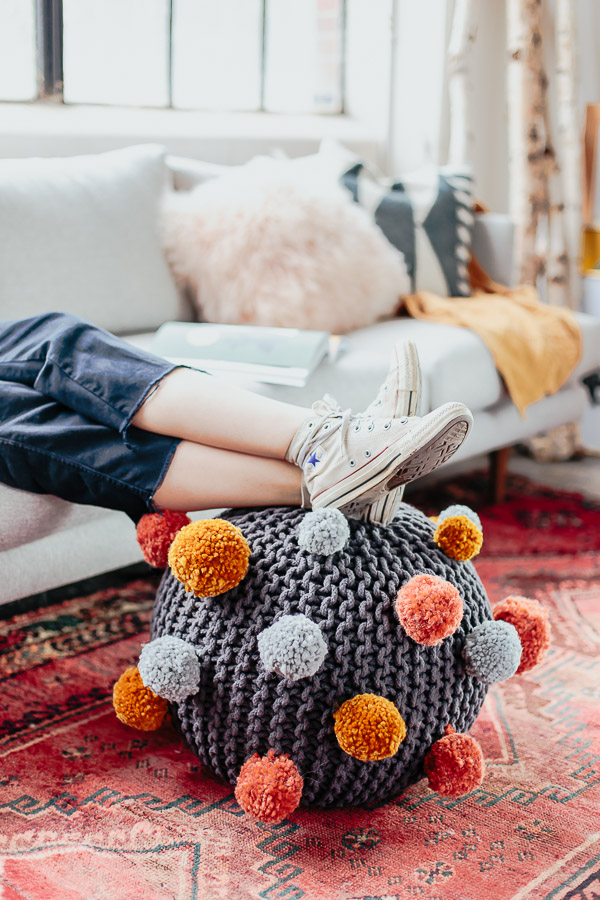 How to make a DIY pom pom ottoman. Click through for the tutorial.
