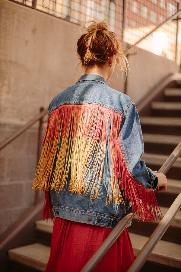 How to embellish a standard jean jacket with fringe, that looks like it was always there! Click through for the tutorial. #fashion #diy #tutorial #fringe #jeanjacket #clothing #womens #fall