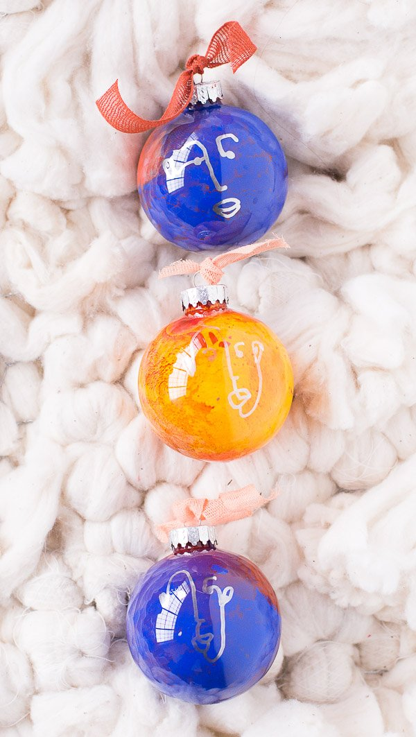 Colorful glass ornaments with hand drawn faces on each one