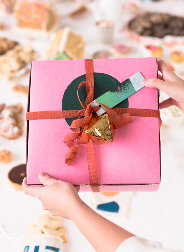 Cute packaging idea for holiday presents. A pink bakery box with a hand painted green circle, rust colored ribbon and a gold geo ornament.
