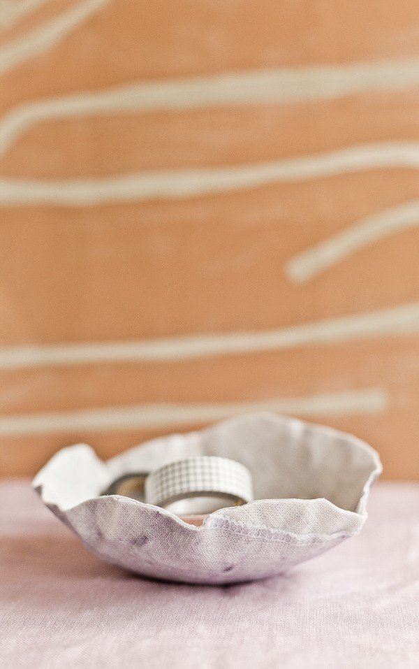 DIY fabric bowl laid on a table with a modern wallpaper background.