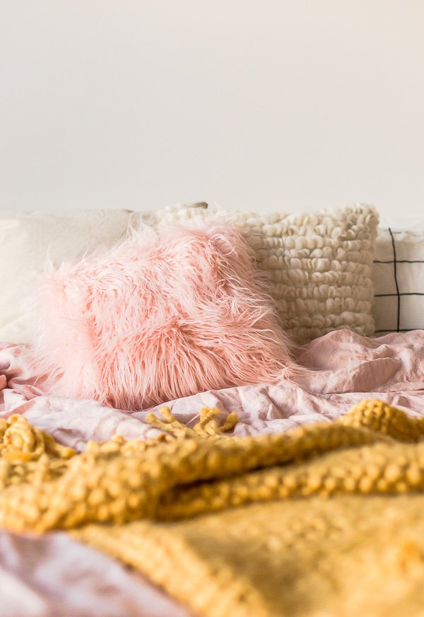 A light-filled, cozy bedroom gets a DIY upgrade with a faux fur pillow project that you can sew up in less than 20 minutes! Wait 'til you see what it's made of! #bedroom #pillow #pink #fauxfur #interiors #interior #decorating #fall #winter #diy