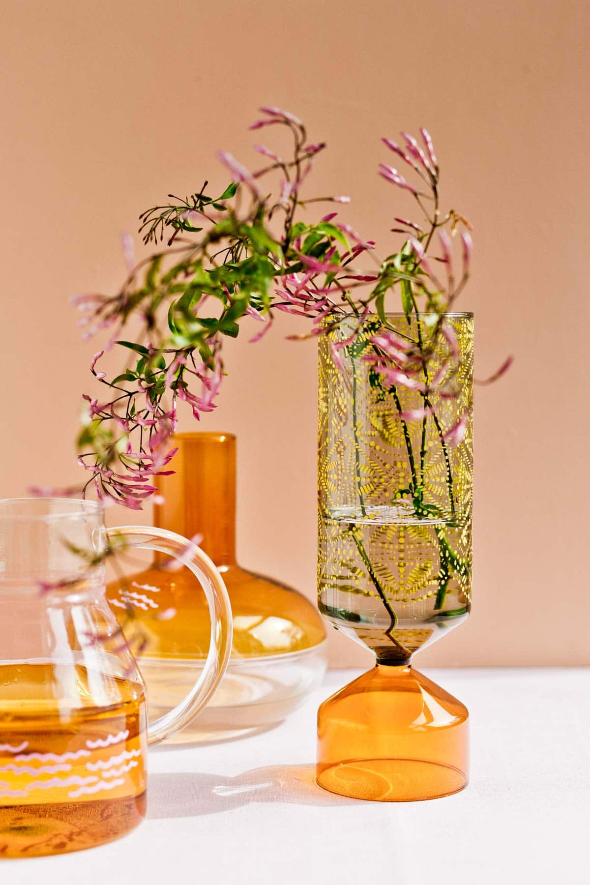 Colorful glass vases and vessels on a table with a neutral background.