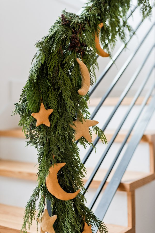 Star ornaments hanging off of Christmas garland on staircase
