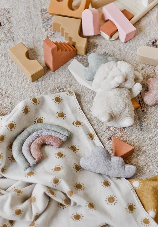 DIY baby toys and gift ideas on the floor with a baby blanketed stuffed animals.