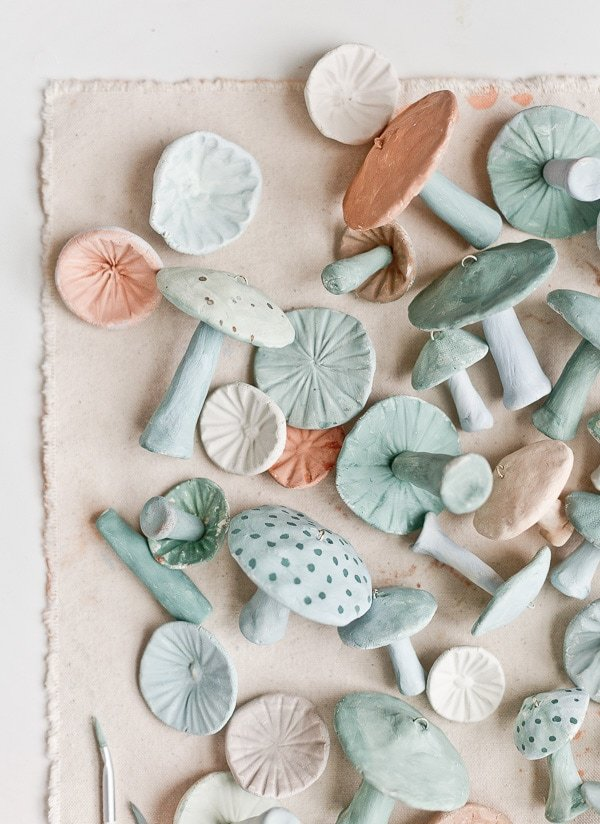 DIY clay mushrooms painted in cool tones on a canvas tablecloth
