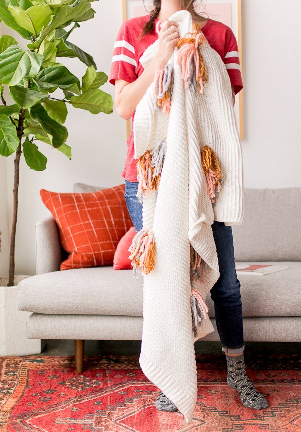 Cozy up with this DIY tassel blanket for winter. It's an easy project, with a little yarn and an existing knit blanket. Click through for the step by step instructions. #diy #blanket #tassel #interiors #homedecor #housewares #cozy #winter