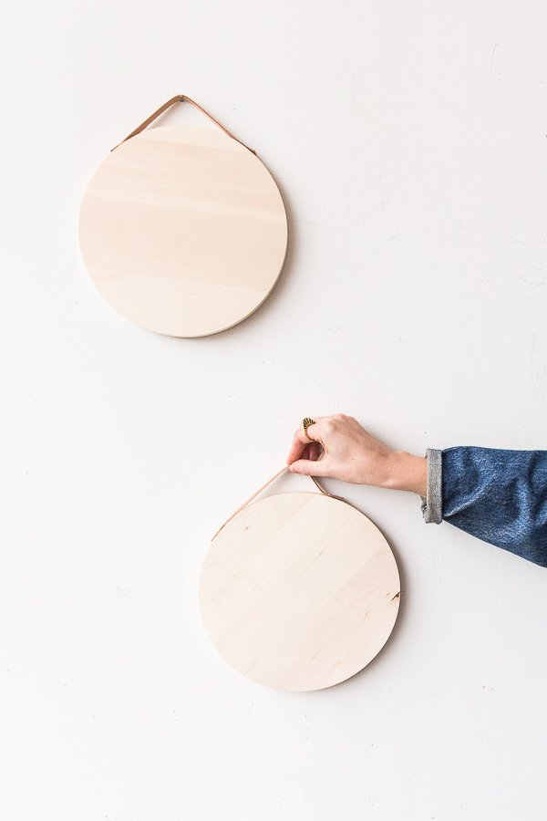 Add leather handles to a wood round and turn it into a DIY serving tray in ten minutes or less. It's easy to hang on the wall and then grab and go when it's ready to use. #servingtray #cheeseboard #entertaining #diy #tutorial #leather #wood