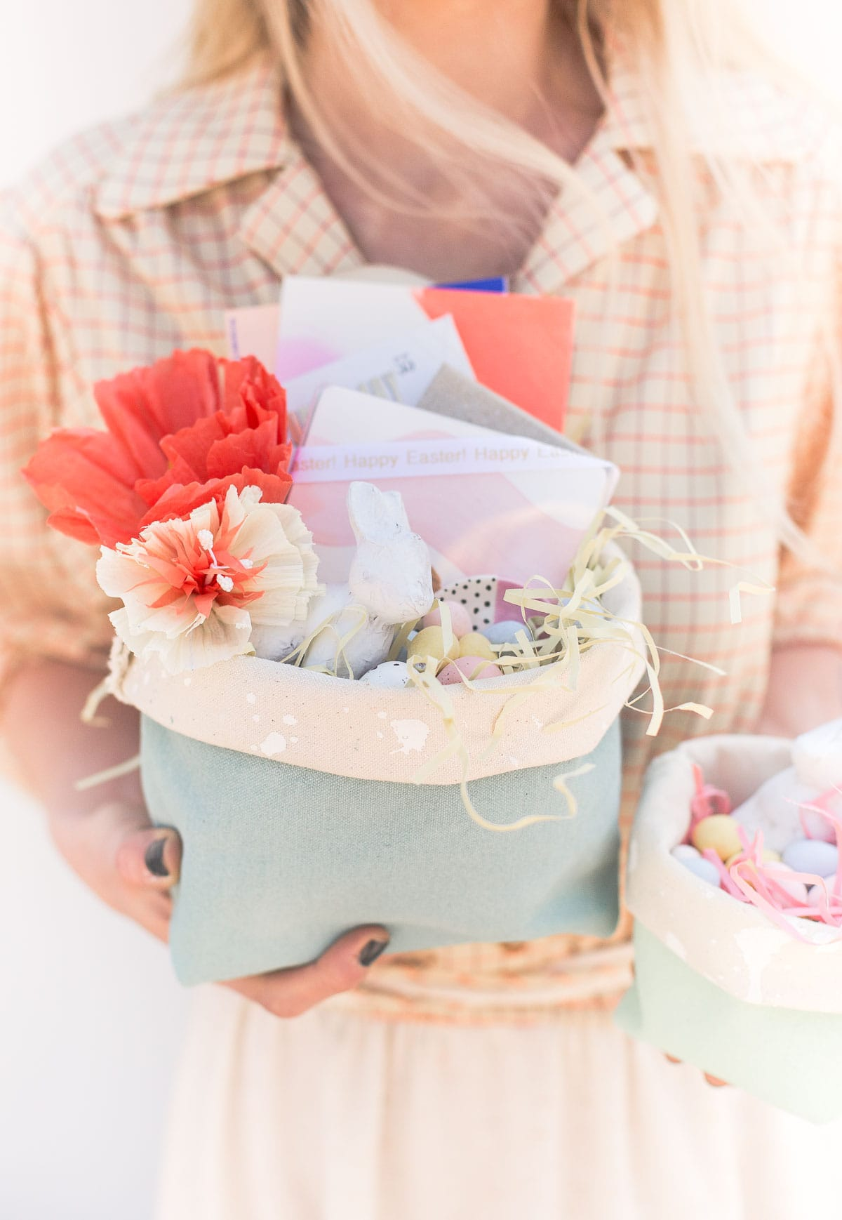 Holding homemade Easter baskets made of canvas, with flowers and candy inside.